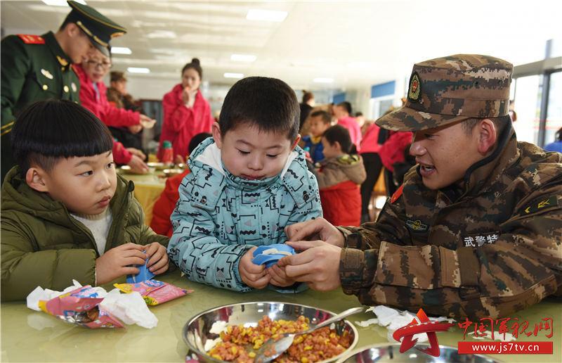 """图18:2019年12月27日,安徽合肥,在武警合肥支队""""军营开放日""""活动现场,战士们在教小军娃包饺子。"""