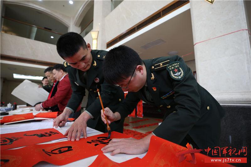 1月20日,粤澳两地书画家走进驻澳军营送上新春祝福,图为官兵代表同书画家们一同书写春联