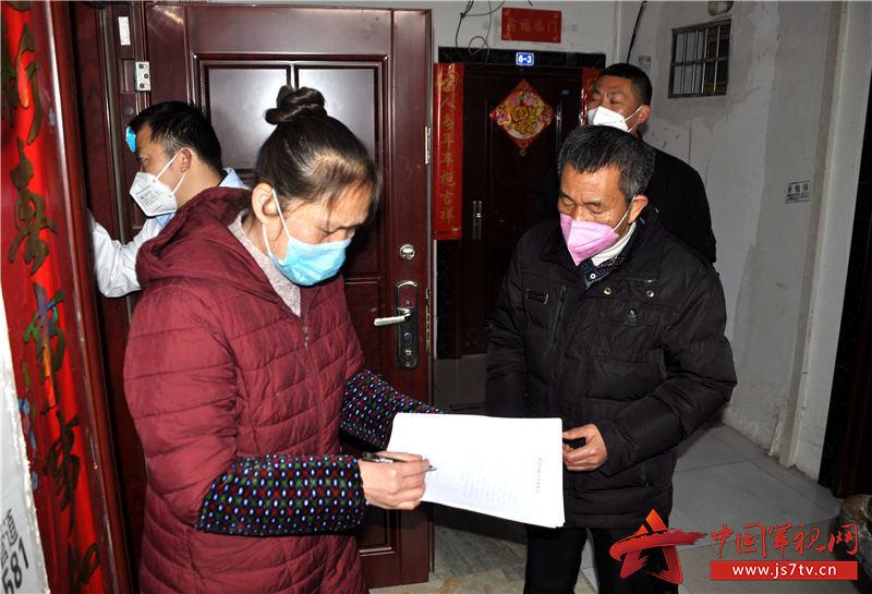 退役军人、老党员王永朋(右一)协助志愿者和医护人员与隔离人员签订解除居家隔离观察承诺书。 (2)