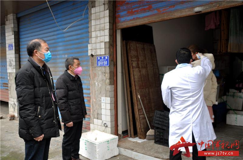退役军人、老党员王永朋(左二)与社区志愿者和医护人员上门对居家隔离对象进行体温检测。