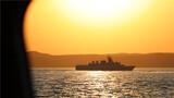 夕阳下的战舰进行机动航行