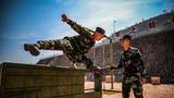 400米障碍训练中,官兵快速飞跃矮墙