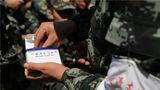 随队卫生员向战士发放防暑药品