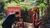 吉克石乌(左)在村口森林草原防火检查点查看进出人员登记情况(5月9日摄)。