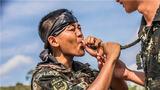 训练途中,一名特战队员借用战友的水袋补充水源。