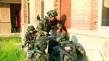 特战队员利用破门器材突入房屋。