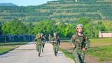 特战队员集体协作负重进行长途奔袭。