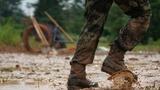 7月11日,在鄱阳县鄱阳镇江家岭村,一名武警战士在搬运沙袋时脚下溅起泥水。新华社记者 周密 摄