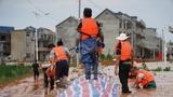 7月11日,在鄱阳县鄱阳镇江家岭村,来自鄱阳县城管局的党员干部在堤坝上给防水墙铺设防水布,防止河水侵蚀墙体。新华社记者 张浩波 摄