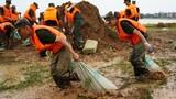 7月11日,武警战士在鄱阳县鄱阳镇江家岭村搬运沙袋。新华社记者 周密 摄