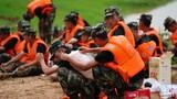 7月11日,武警战士们在休息时互相涂抹药粉,连日奋战让许多战士长痱子或晒伤。新华社记者 周密 摄