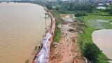 7月11日,抢险人员在堤坝上给防水墙铺设防水布,防止河水侵蚀墙体(无人机照片)。新华社记者 张浩波 摄