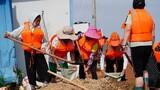 7月11日,鄱阳县鄱阳镇江家岭村的村民们在装填沙袋。新华社记者 周密 摄