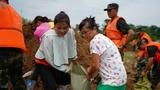 7月11日,在鄱阳县鄱阳镇江家岭村,村民们与武警官兵一起搬运沙袋。新华社记者 周密 摄