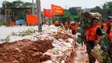 7月11日,武警战士在鄱阳县鄱阳镇江家岭村搬运编织袋,他们身旁的河水几乎要漫过防水墙上沿。新华社记者 周密 摄