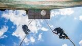 预备特战队员在进行18米抓绳攀登训练。