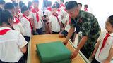 武警官兵教同学们叠军被。