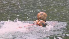 为了架设一条空中溜索,他身栓绳索从冰山融水中只身过河