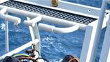 潜水员通过吊笼入水。