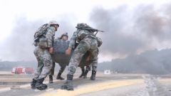 大火封路 浓烟呛鼻 汽车兵徒手搬运200公斤轮胎通过窄桥